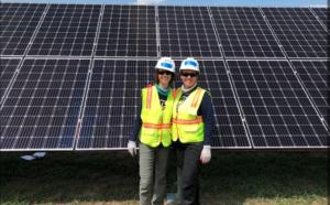 Two women in front of community solar array