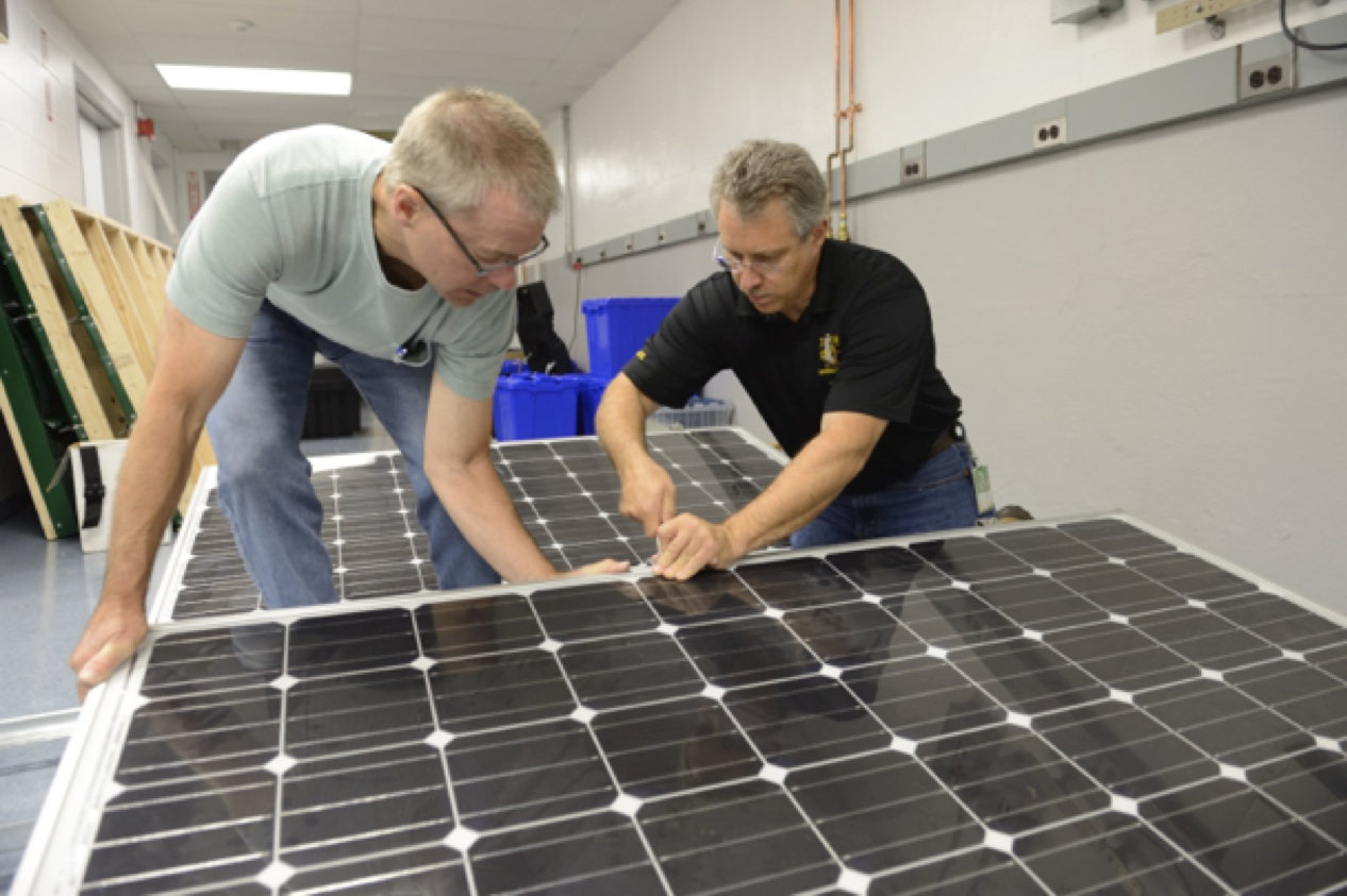 Two instructor trainees practice with commercial flat roof ballast mounts.  Job well done!!