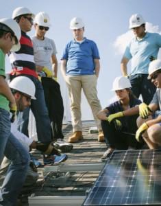 Andy Mackey of UMC Solar teaches internship program students how to install solar panels on the sloped roof of training facility.