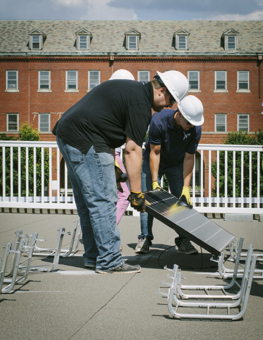 Kevin Wright of UMC Solar assists one of the students in mounting the panel onto the racking system correctly.