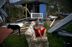 Angel Rodriguez poses next to his belongings in front of his house, destroyed by Hurricane Maria, in the San Lorenzo neighborhood of Morovis, Puerto Rico, Saturday, Sept. 30, 2017.